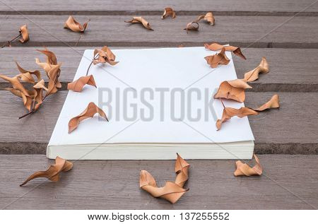 Closeup white note book on wooden table in the garden with dried leaves textured background