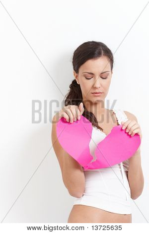 Heart-broken woman holding a paper heart in hands, looking sadly.?