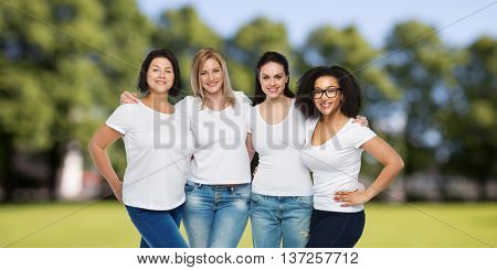 friendship, diverse, body positive and people concept - group of happy different size women in white t-shirts hugging over summer park background