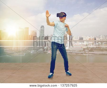 3d technology, virtual reality, entertainment, cyberspace and people concept - young man with virtual reality headset or 3d glasses playing game and fighting over singapore city skyscrapers background