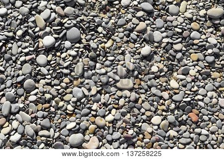 closeup of a background of pebbles of a shingle beach or of the bank of a river