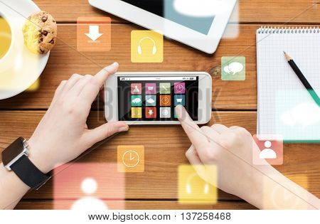 technology, business, people and media concept - close up of woman with menu icons on smartphone screen and coffee cup on wooden table