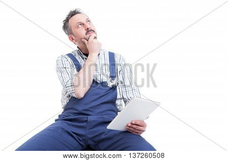 Pensive Mechanic With Tablet Looking For Solution