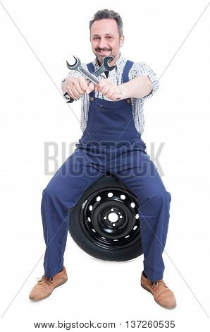 Smiling Handsome Mechanic With Wrench Sitting On Tire