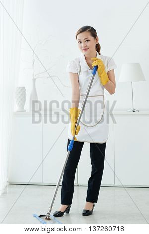 Vietnamese maid cleaning floor in the room