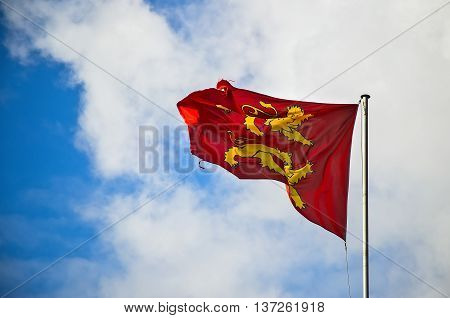Normandy flag flying in the wind under blue skies
