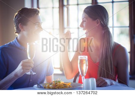 Young woman feeding her man at dining table in the restaurant