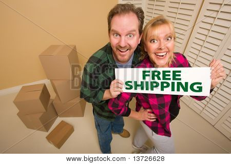 Goofy Couple Holding Free Shipping Sign in Room with Packed Cardboard Boxes.