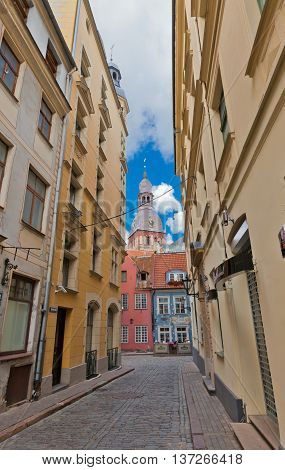 RIGA LATVIA - JULY 05 2016: Old narrow Kramu Street in the historic center of Riga Latvia with belfry of Dome Cathedral on the background. World Heritage Site of UNESCO