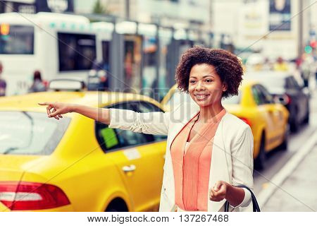 business trip, transportation and people concept - young smiling african american woman catching taxi at city street