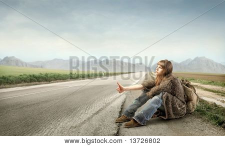 Woman hitchhiking on a countryside road