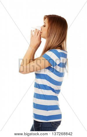 Teen woman with allergy or cold blowing nose