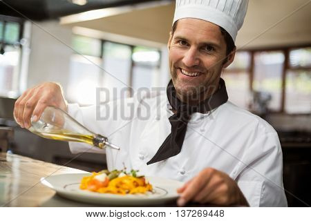 Portrait of happy chef pouring olive oil on meal in commercial kitchen