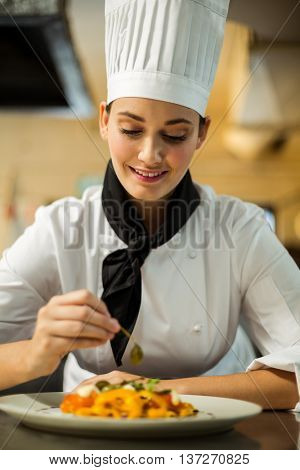 Happy head chef garnishing pasta dish with olive in commercial kitchen