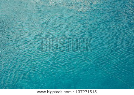 turquoise water in the pool with wawes background