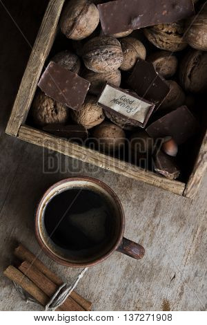 good morning idea - text and a cup of coffee, chocolate and nuts on the vintage table