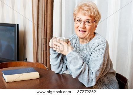 Senior woman sitting at the desk with book and drinking tea or coffee