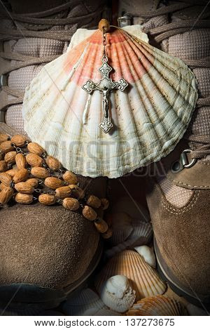 Scallop shell with a wooden rosary beads with a silver crucifix over a pair of hiking boots. Symbols of the Christian pilgrimage