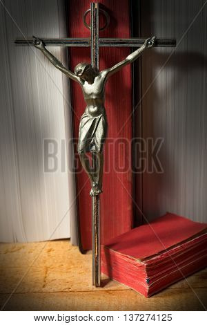 Silver crucifix (Christ on the cross) and two Holy Bibles with red pages in a library with books with white paper