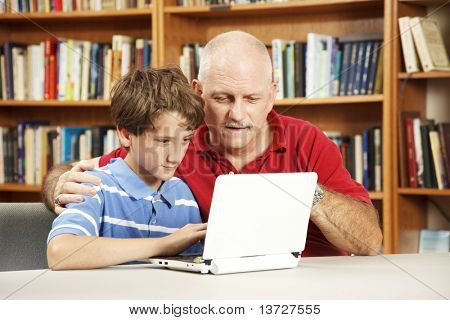 Teacher helping a student use a netbook computer in the school library.