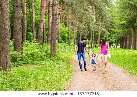 Happy young family walking down the road outside in green nature