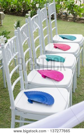 white chair decoration in wedding celebration with colorful of fan
