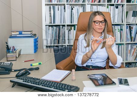 Portrait of bored blonde secretary polishing nails at workplace