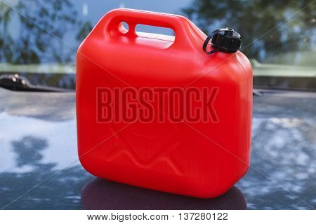 Red Plastic Jerry Can Stands On Car Hood