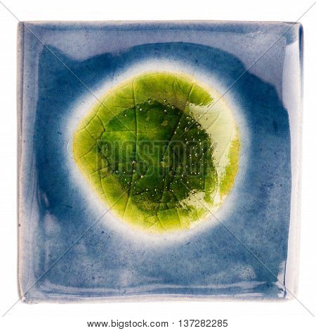 Blue handmade glazed ceramic tile with big green dot in middle isolated on white