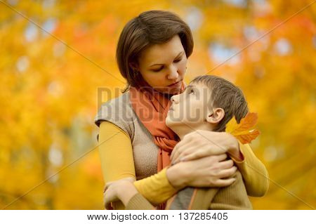 Sad mother with a son on a walk during the fall of the leaves in the park