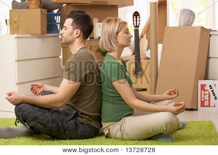 Young couple sitting in yoga meditation posture on carpet in new house, surrounded with boxes.?