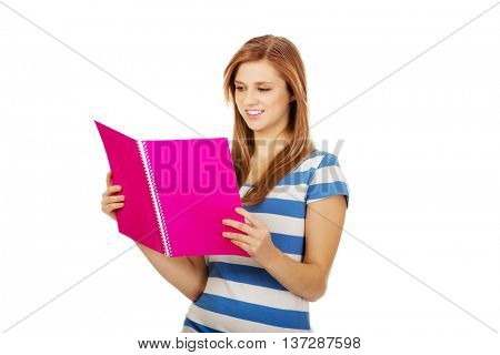 Pretty teenage woman reading her notes