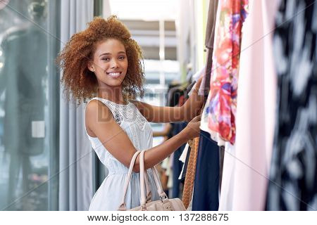 Portrait of an attractive young woman with curly hair browsing through clothes hanging on racks while standing in a clothing store