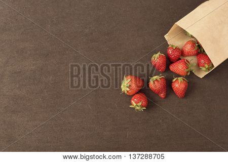 Paper Bag With Fresh Red Strawberries. Fresh Strawberries In A Small Bag On A Wooden Style Surface.