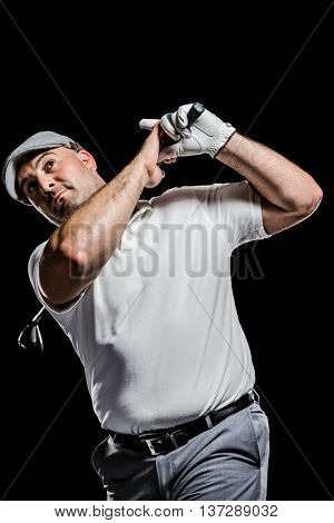 Portrait of golf player taking a shot on black background