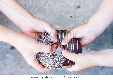 children's hands holding a chocolate donut. two kids pull to themselves donut. close-up.the concept of sharing food