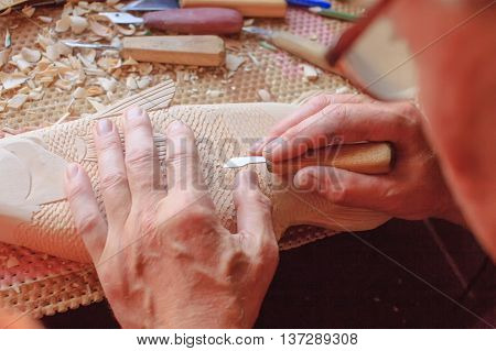 master carves wooden fish. woodcarving closeup. craft and creative