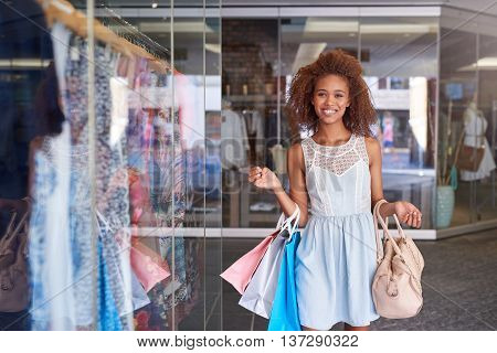 Attractive young woman with curly hair smiling and carrying shopping bags while enjoying a day shopping at the mall