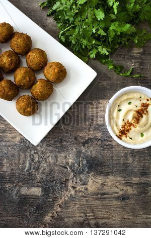 Falafels,lettuce and hummus on a rustic wooden background