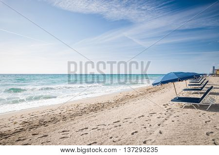 Beach in Miami FL. Open umbrellas on the sand beach at the ocean. Empty beach. Sea shore. Early morning. Clouds background.