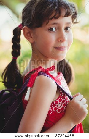 Girl holding strap of her bag in a park on a sunny day