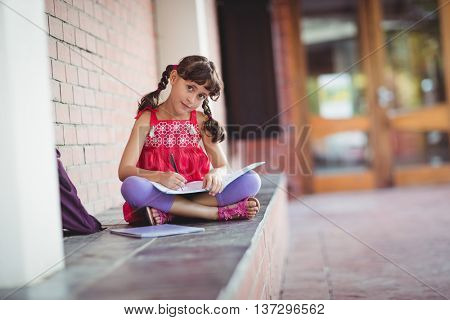 Girl writting in a book with legs crossed