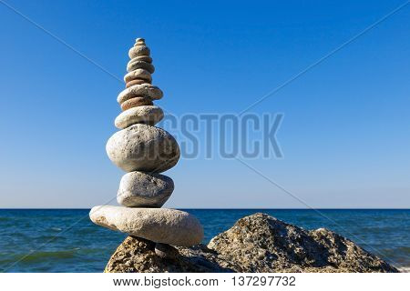 Concept of harmony and balance. Rock Zen on the background of summer sea