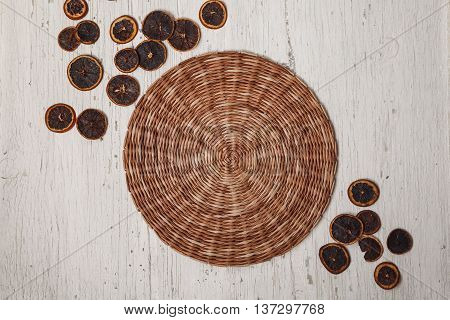 Wicker brown place mat with dried lemons.