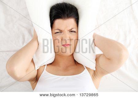 Feminino deitado na cama e fechar seus ouvidos com o travesseiro.  Insônia