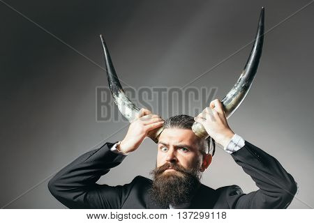 Handsome young man with long beard and moustache in black jacket holding animal antlers in studio on grey background