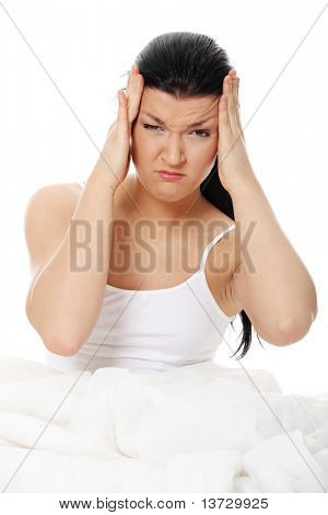 Young caucasian female sitting on bed. She have terrible headache (illness or hangover). Isolated on white