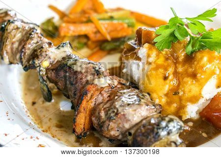 South african lunch served in an open air barbecue restaurant: Springbok skewer grilled with a curry sauce carrot and aspargus side dish and semolina dumpling with coriander decoration.