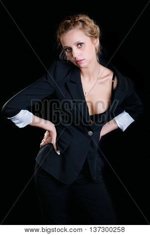 The girl in a black brassiere against dark background