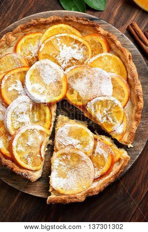 Pie with orange caramelized slices on wooden background top view
